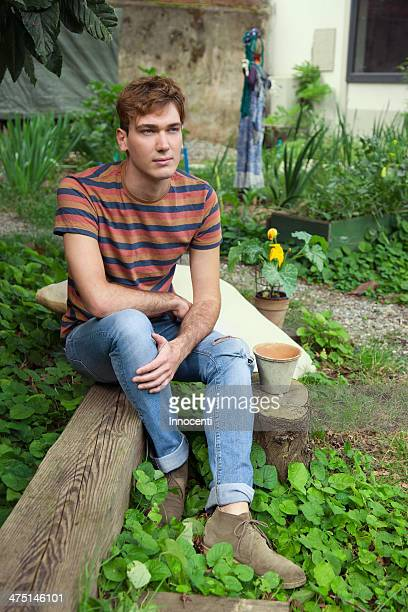 Young man sitting by vegetable garden