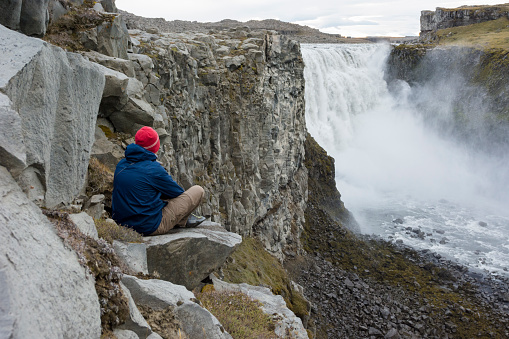 Young man sitting down looking at Detifoss waterfall in Iceland. - gettyimageskorea