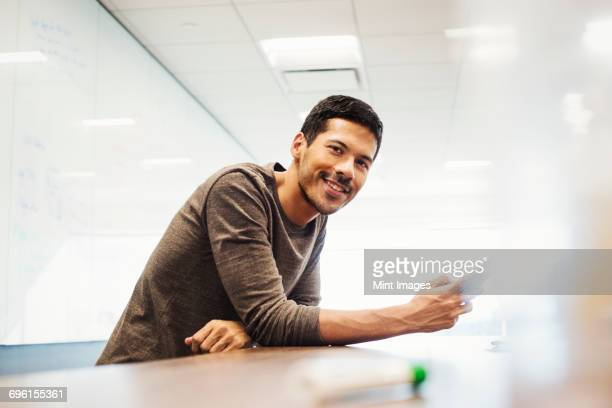 A young man sitting in a classroom leaning on a desk and smiling.