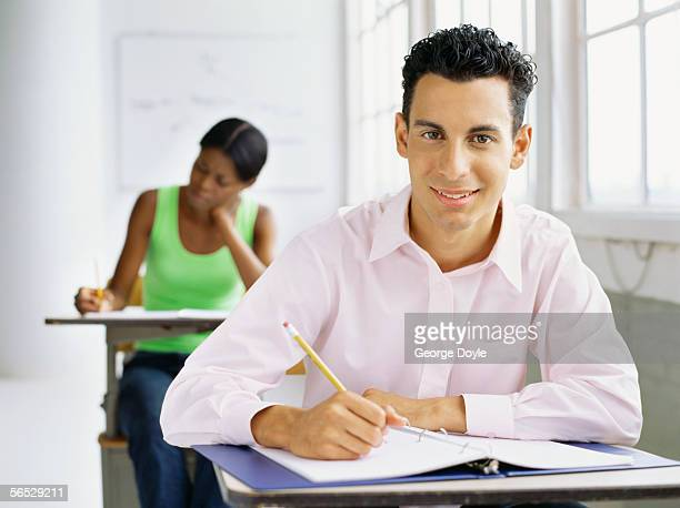 young man sitting in a classroom with another student
