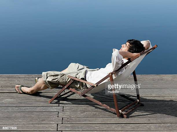 A young man sitting in a deck chair on a jetty