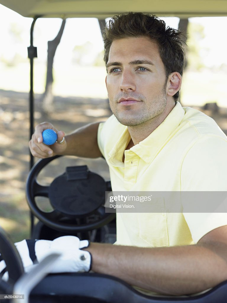 Young Man Sitting in a Golf Buggy Holding a Golf Ball : Stock Photo