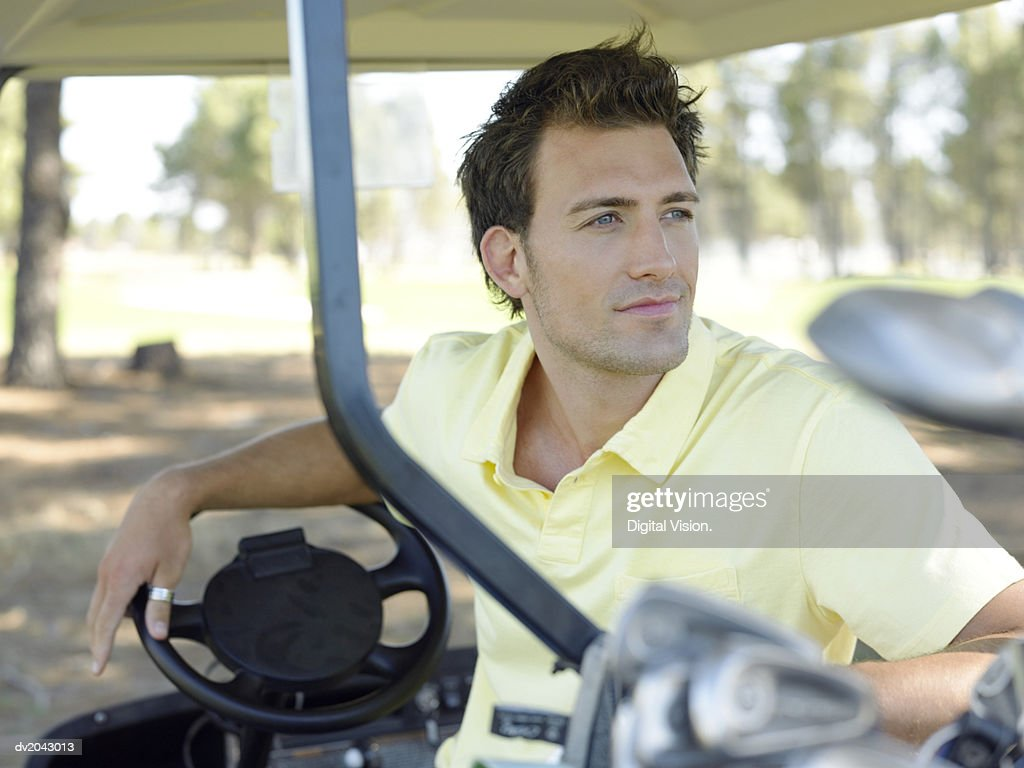 Young Man Sitting in a Golf Buggy : Stock Photo