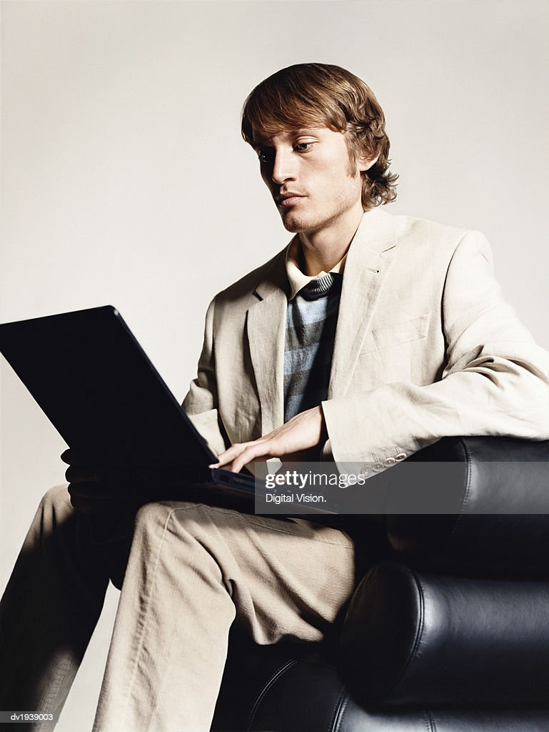 Young Man Sitting in a Leather Arm Chair Using a Laptop Computer : Stock Photo