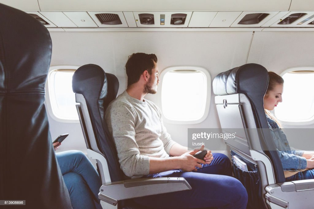 Young man sitting in airplane near window : Stock Photo