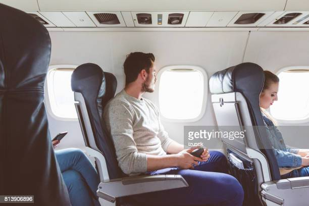 young man sitting in airplane near window - vehicle interior stock pictures, royalty-free photos & images