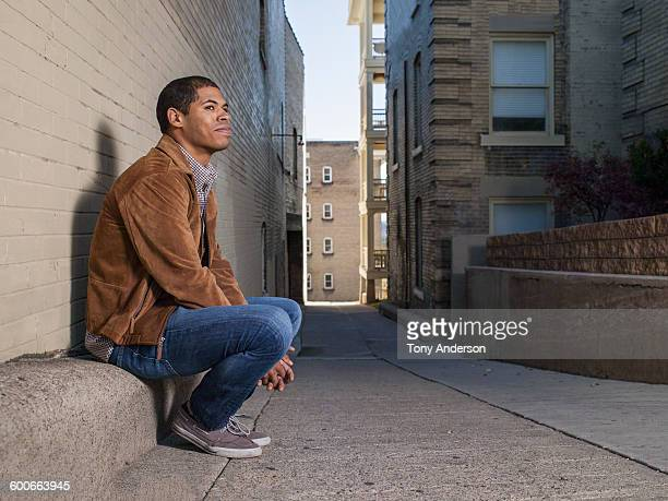 young man sitting in an alley in the city - suede stock pictures, royalty-free photos & images