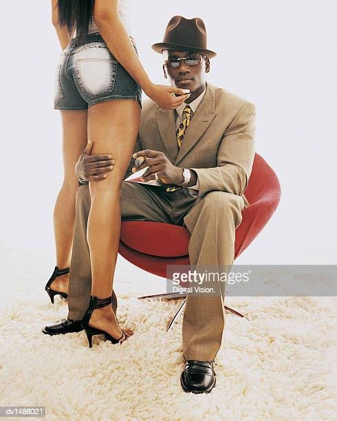 Young Man Sitting in an Armchair Holding the Leg of a Woman Standing by Him