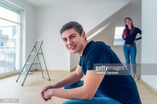 young man sitting in an empty room in his new apartment. in the background his girlfriend, a stepladder and a large window. relocation / new beginning concept. moving house concept. - mortgage stock pictures, royalty-free photos & images