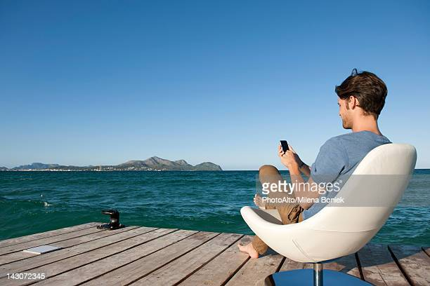Young man sitting in armchair by lake using cell phone, side view