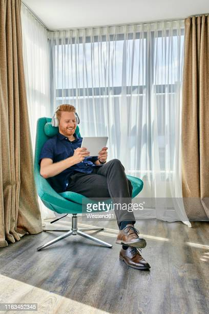 young man sitting in armchair, listening music, using digital tablet - mood stream stock pictures, royalty-free photos & images