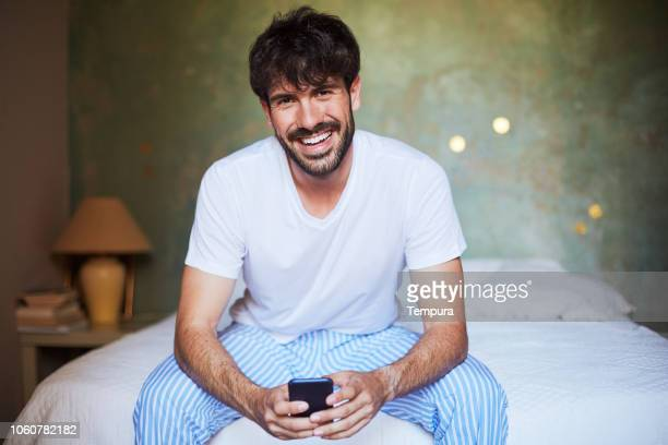 Young man sitting in bed with phone looking at camera.