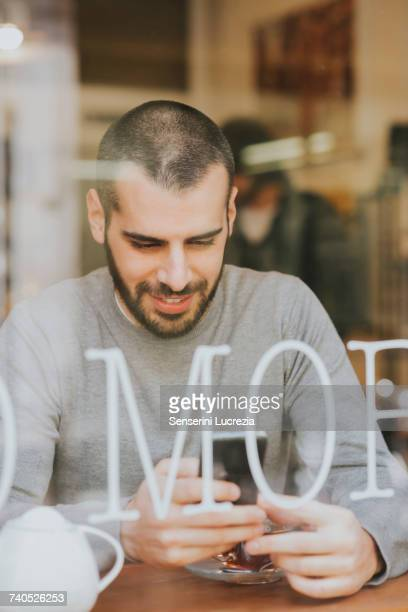 young man sitting in cafe, using smartphone, view through window - muro stock photos and pictures