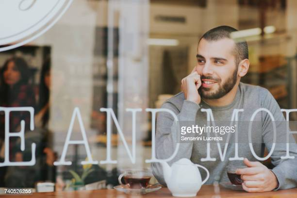 young man sitting in cafe, view through window - muro stock photos and pictures