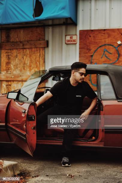 Young Man Sitting In Car With Door Open On Road