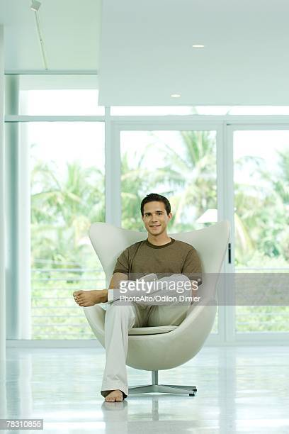 young man sitting in chair holding book, smiling at camera - medium shot stock pictures, royalty-free photos & images