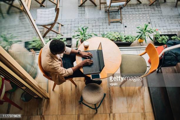 コーヒーショップに座ってラップトップを使う若者 - オープンカフェ ストックフォトと画像