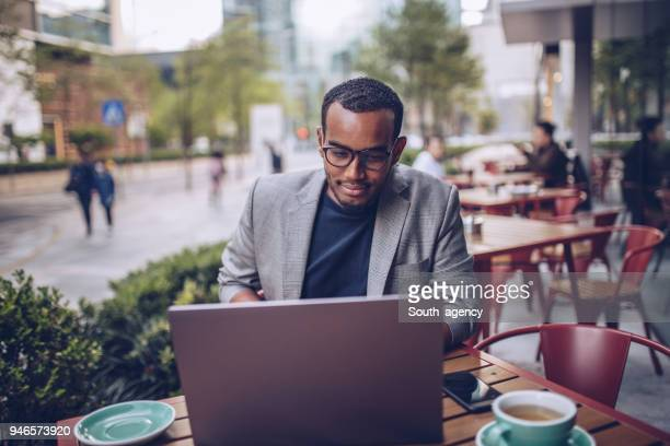 young man sitting in coffee shop and using laptop - pavement cafe stock pictures, royalty-free photos & images