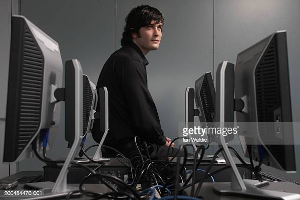 Young man sitting in computer room looking away