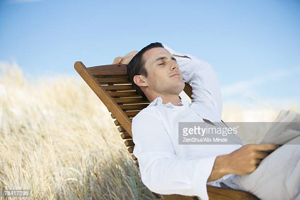 Young man sitting in deck chair, napping