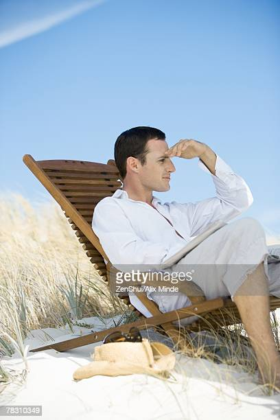 Young man sitting in deck chair on beach, shading eyes