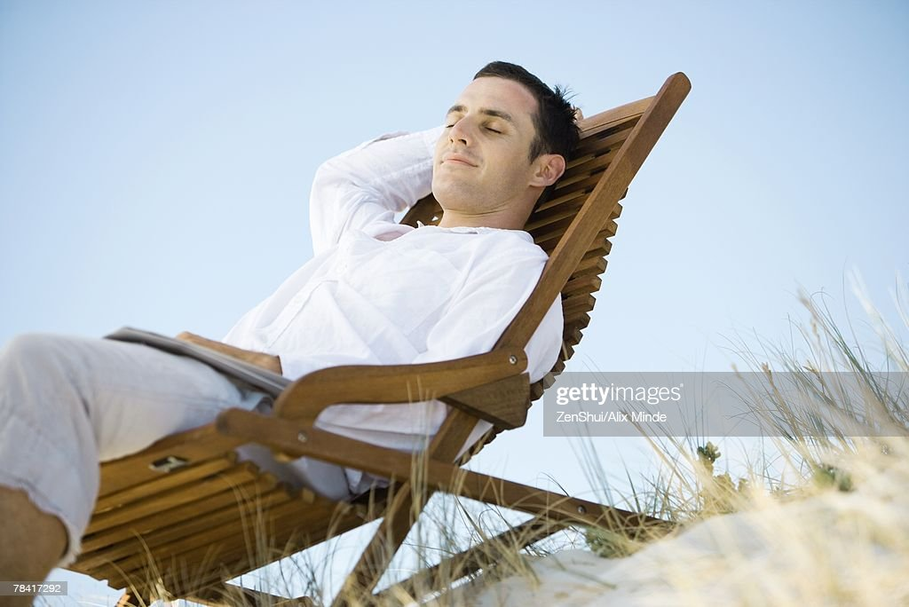 Young man sitting in deck chair, smiling, low angle view : Stock-Foto