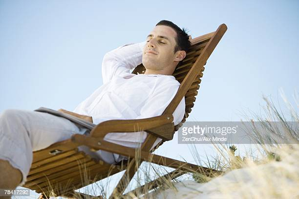 Young man sitting in deck chair, smiling, low angle view