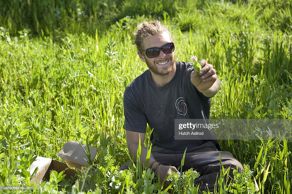 Young man sitting in field : Stockfoto