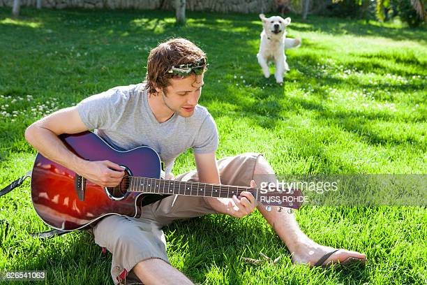 Young man sitting in garden playing acoustic guitar
