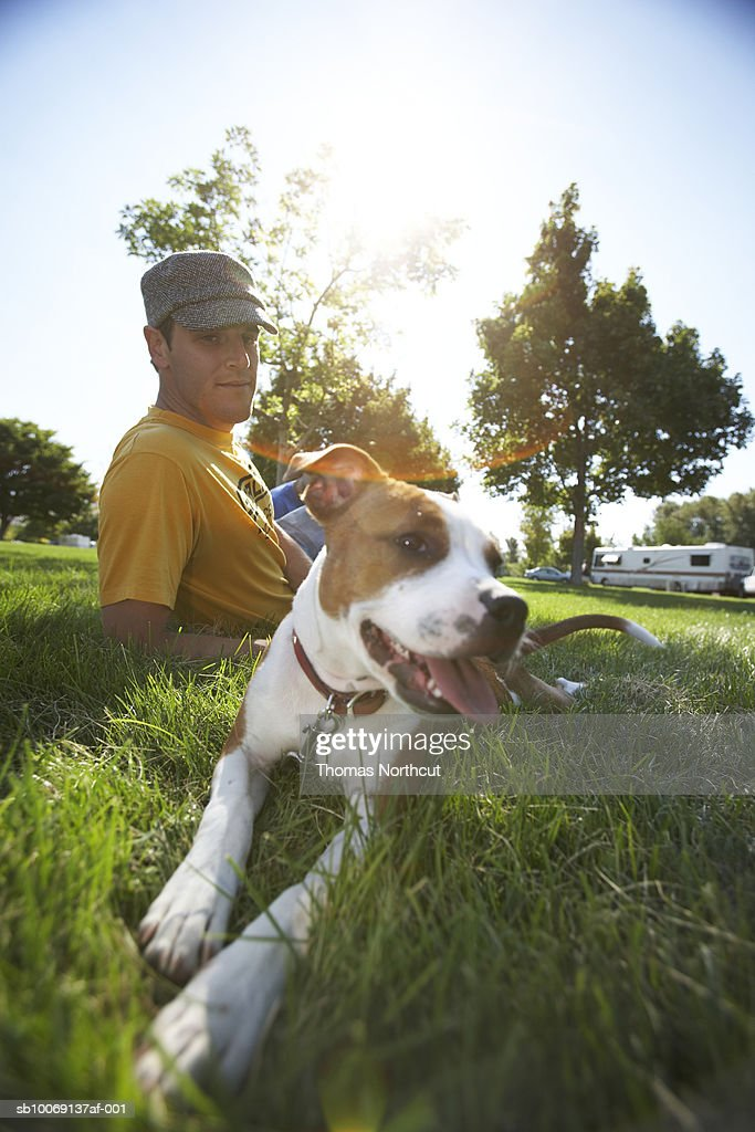 Young man sitting in grass with stratford terrier puppy : Stockfoto
