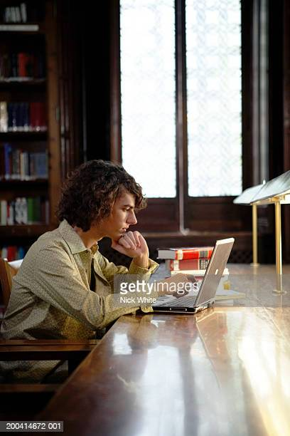 Young man sitting in libary using laptop under desk lamps