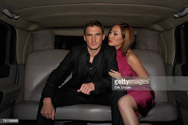 Young man sitting in limousine, woman flirting with him
