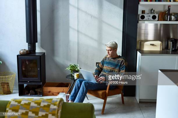 young man sitting in living room using laptop - jumper stock pictures, royalty-free photos & images