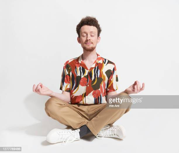 young man sitting in mediation pose - relaxation stock pictures, royalty-free photos & images