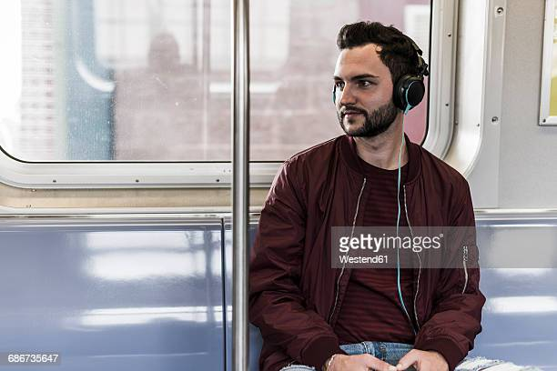 Young man sitting in subway wearing headphones