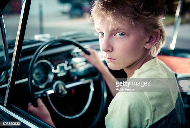 a young man sitting in the driver's seat of a vintage car - robb reece stockfoto's en -beelden