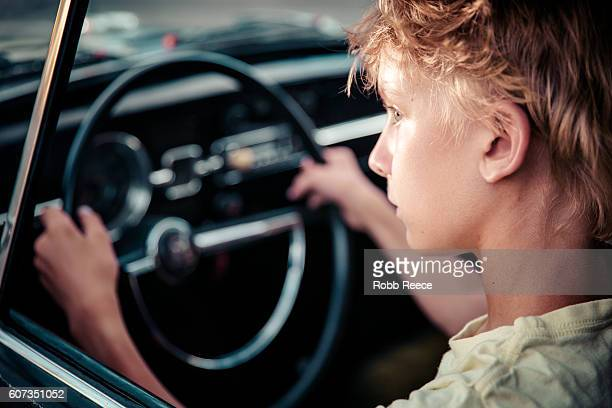 a young man sitting in the driver's seat of a vintage car - robb reece stock pictures, royalty-free photos & images