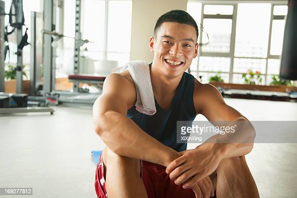 Young man sitting in the gym, portrait