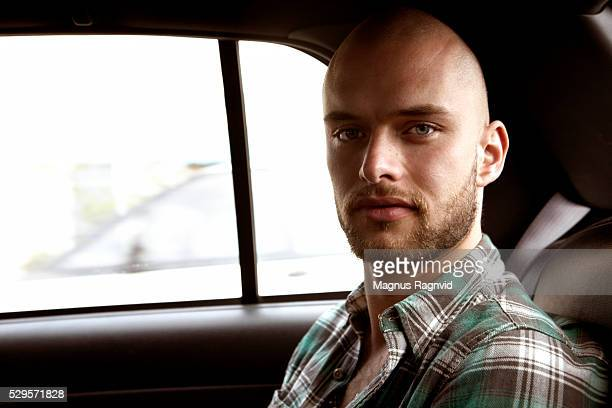 Young man sitting inside taxi