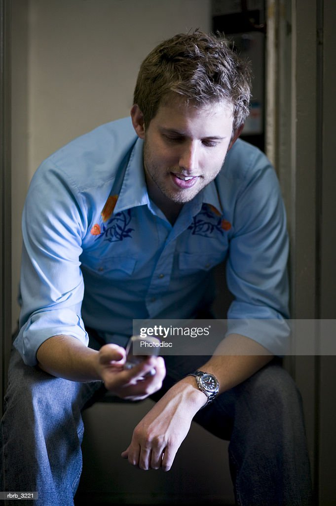 Young man sitting looking at a mobile phone : Foto de stock