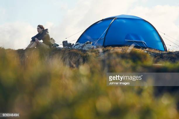 young man sitting near tent - man made structure stock pictures, royalty-free photos & images