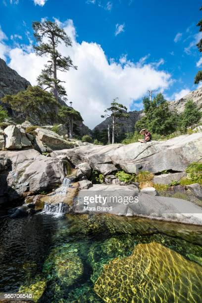 young man sitting next to a pool with small waterfall in the mountains, river golo, nature park of corsica, parc naturel regional de corse, corsica, france - corsica stock-fotos und bilder