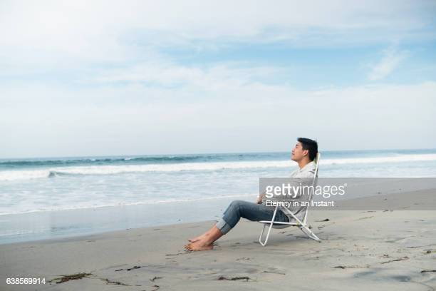 WS Young man sitting on a beach chair by the sea