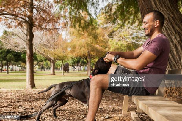 Young man sitting on a bench playing with his dog.