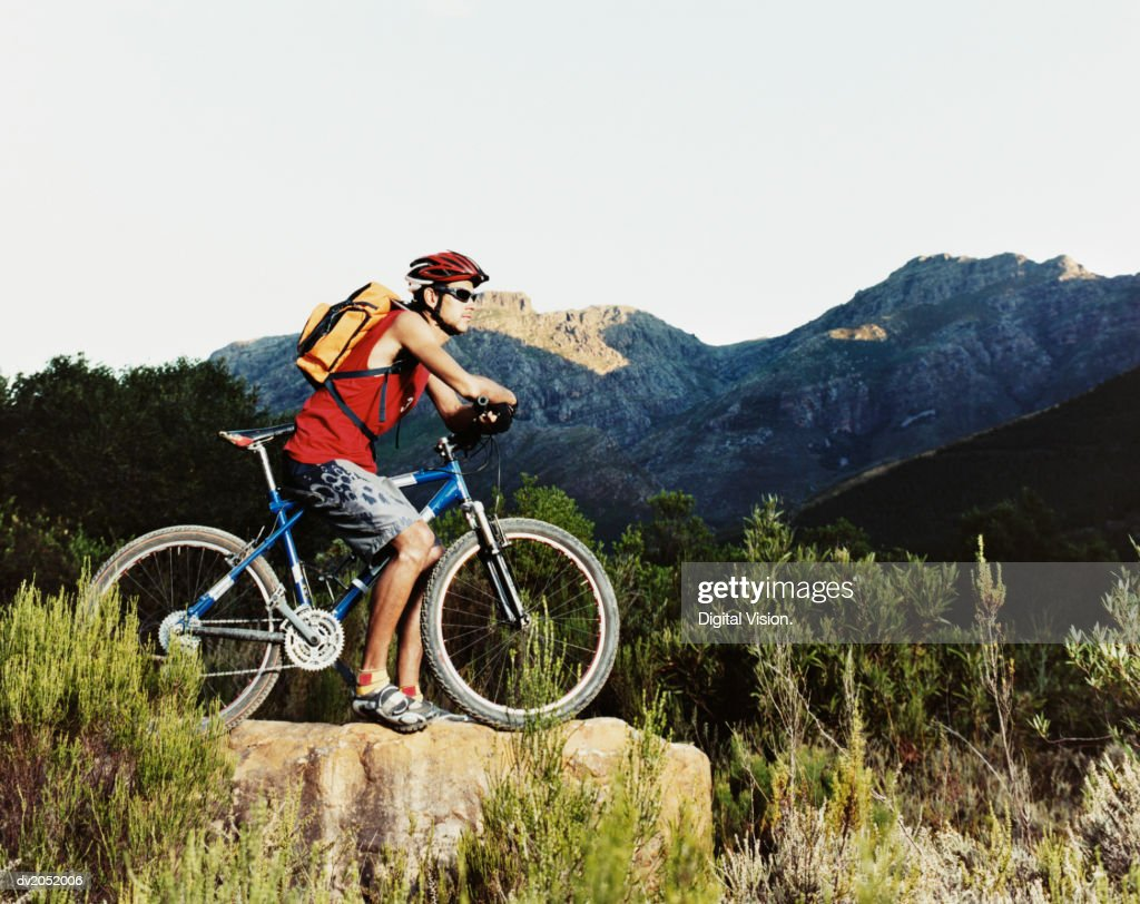 Young Man Sitting on a Bike and Looking at a View of Mountains : Stock Photo