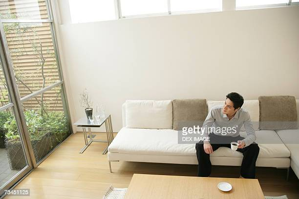 Young man sitting on a couch and holding a cup of coffee