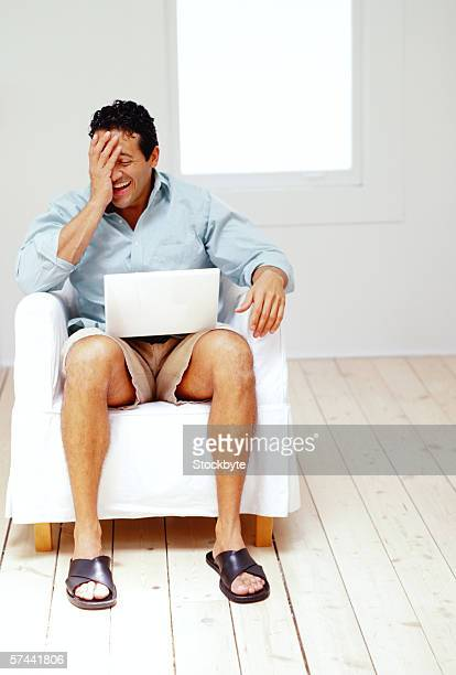young man sitting on a couch in front of a laptop and laughing - pantaloncini foto e immagini stock