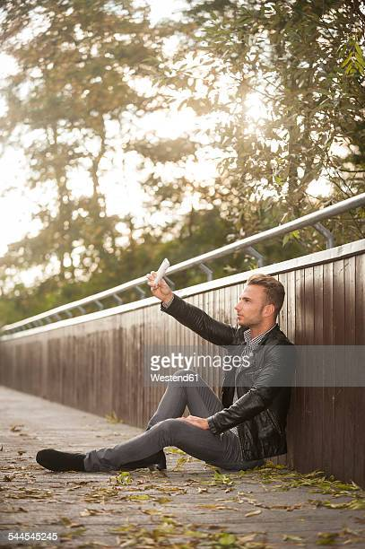 Young man sitting on a footbridge taking a selfie with his smartphone