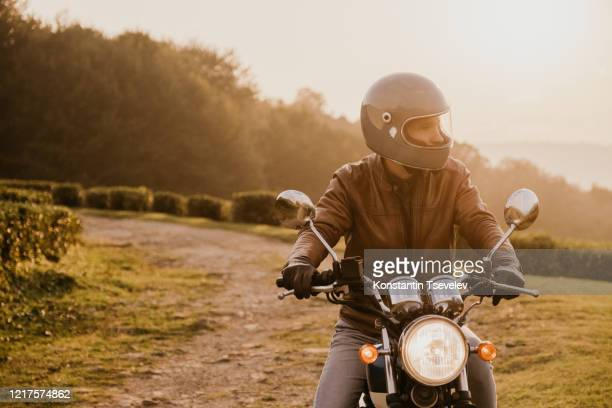 young man sitting on a motorcycle at sunset - ecchi biker stock pictures, royalty-free photos & images