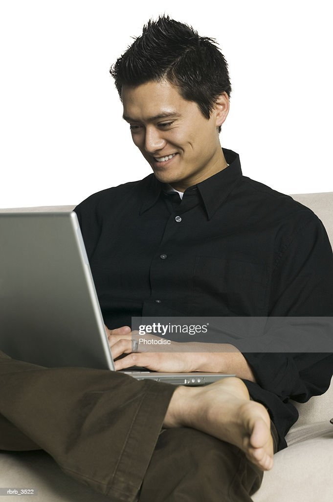 Young man sitting on a sofa using a laptop : Foto de stock